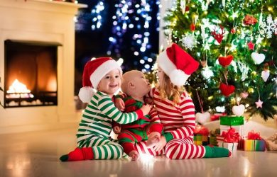 Happy little kids in matching red and green striped pajamas decorate Christmas tree in beautiful living room with traditional fire place. Children opening presents on Xmas eve.